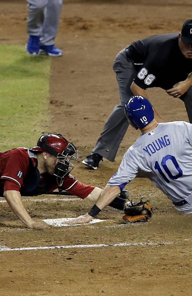 Los Angeles Dodgers third baseman Michael Young (10) slides across the plate as Arizona Diamondbacks catcher Miguel Montero applies the tag during the sixth inning of a baseball game, Wednesday, Sept. 18, 2013, in Phoenix. Young was called out on the play