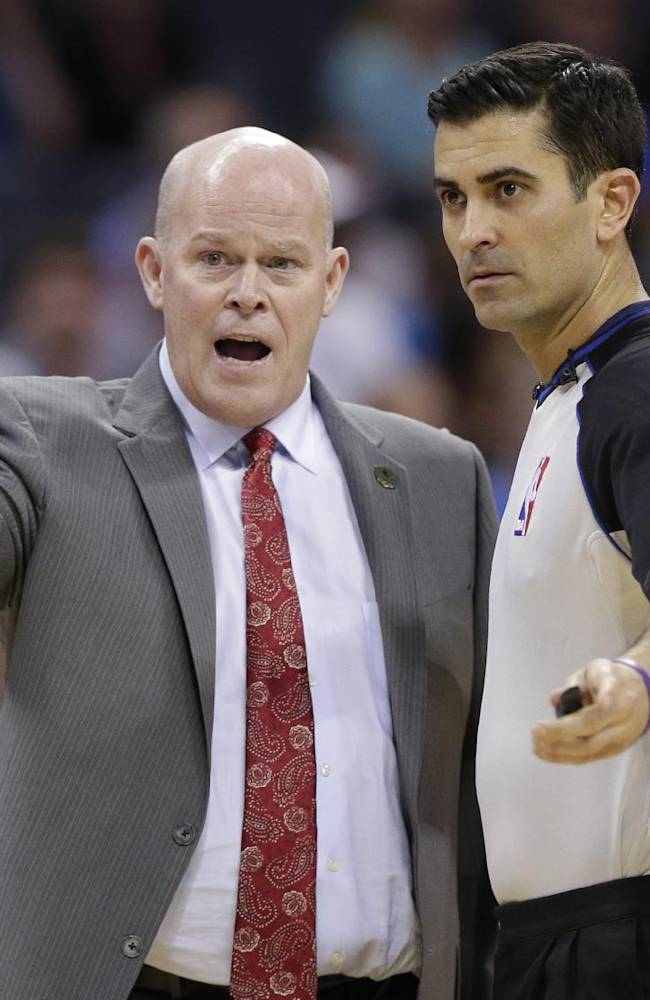 Charlotte Bobcats head coach Steve Clifford, left, complains to referee Tommy Nunez Jr, right, during the first half of an NBA basketball game against the Orlando Magic in Charlotte, N.C., Friday, April 4, 2014