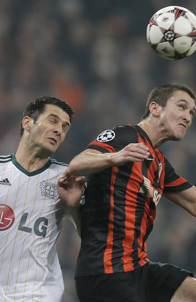 Donetsk's Ferreyra Facundo, right, and Leverkusen's Emir Spahic challenge for a high ball during the Champions League group A soccer match between Bayer 04 Leverkusen and FC Shakhtar Donetsk  at the Donbas Arena stadium in Donetsk, Ukraine, Tuesday, Nov. 5, 2013