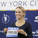 Professional tennis player Caroline Wozniacki poses with her runner's bib during a news conference, Wednesday, Oct. 29, 2014, in New York. The Danish tennis star, formerly top-ranked in the world, will run the New York City Marathon, Sunday, Nov. 2, to raise funds for the New York Road Runners Team for Kids charity, which promotes youth running. (AP Photo/Mark Lennihan)