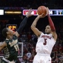 Louisville's Peyton Siva, right, puts a shot up over the defense of South Florida's Anthony Collins during the second half of an NCAA college basketball game Saturday, Jan. 12, 2013, in Louisville, Ky. Louisville defeated South Florida 64-38. Siva led all scorers with 17 points. (AP Photo/Timothy D. Easley)