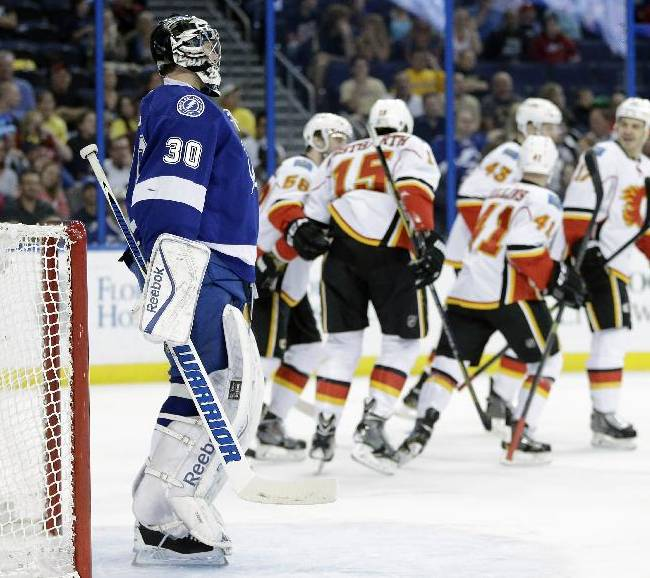 Tampa Bay Lightning goalie Ben Bishop (30) watches as the Calgary Flames celebrate a goal by Kevin Westgarth (15) during the first period of an NHL hockey game on Thursday, April 3, 2014, in Tampa, Fla