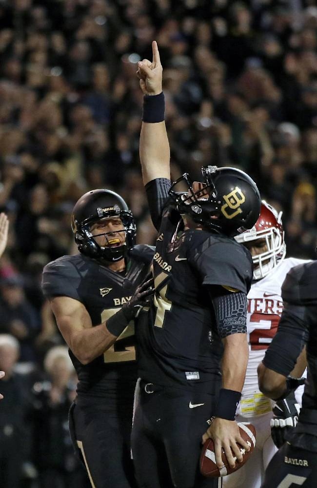Baylor 's Clay Fuller, left, celebrates with quarterback Bryce Petty, pointing to the sky after Petty kept the ball on a running play for a score against Oklahoma in the first half of an NCAA college football game, Thursday, Nov. 7, 2013, in Waco, Texas