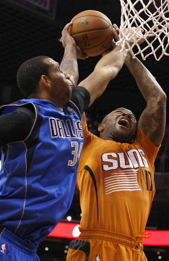 Dallas Mavericks power forward Brandan Wright (34) fouls Phoenix Suns small forward P.J. Tucker (17) in the third quarter during an NBA basketball game, Friday, Jan. 17, 2014, in Phoenix