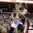 Cleveland Cavaliers' Andrew Bynum (21) drives past Portland Trail Blazers' Robin Lopez during the second quarter of an NBA basketball game Tuesday, Dec. 17, 2013, in Cleveland. (AP Photo/Tony Dejak)