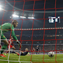 Bayern's Thomas Mueller, centre in red, scores his sides second goal past Manchester United's goalkeeper David de Gea during the Champions League quarterfinal second leg soccer match between Bayern Munich and Manchester United in the Allianz Arena in Muni