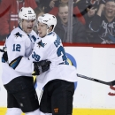 San Jose Sharks' Patrick Marleau, left, celebrates with Logan Couture his game-winning goal against the Calgary Flames during the third period of an NHL hockey game in Calgary, Alberta, Saturday, Dec. 6, 2014 The Associated Press