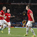 Manchester United's Phil Jones, right, celebrates with teammatesafter scoring the opening gaol during their Champions League group A soccer match between Manchester United and Shakhtar Donetsk at Old Trafford Stadium, Manchester, England, Tuesday, Dec. 10