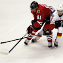 Chicago Blackhawks right wing Marian Hossa (81) battles for the puck against Calgary Flames left wing Johnny Gaudreau (13) during the third period of an NHL hockey game in Chicago, Sunday, Dec. 14, 2014. The Blackhawks won 2-1 The Associated Press