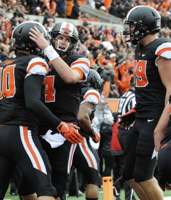 Oregon State's quarterback Sean Mannion (4) congratulates Caleb Smith (10) on his touchdown reception against Colorado in the first half of an NCAA college football game on Saturday, Sept 28, 2013, in Corvallis, Ore