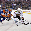 Chicago Blackhawks' Jonathan Toews (19) is chased by Edmonton Oilers' Matt Hendricks (23) and Andrew Ference (21) during the first period of an NHL hockey game Friday, Jan. 9, 2015, in Edmonton, Alberta The Associated Press