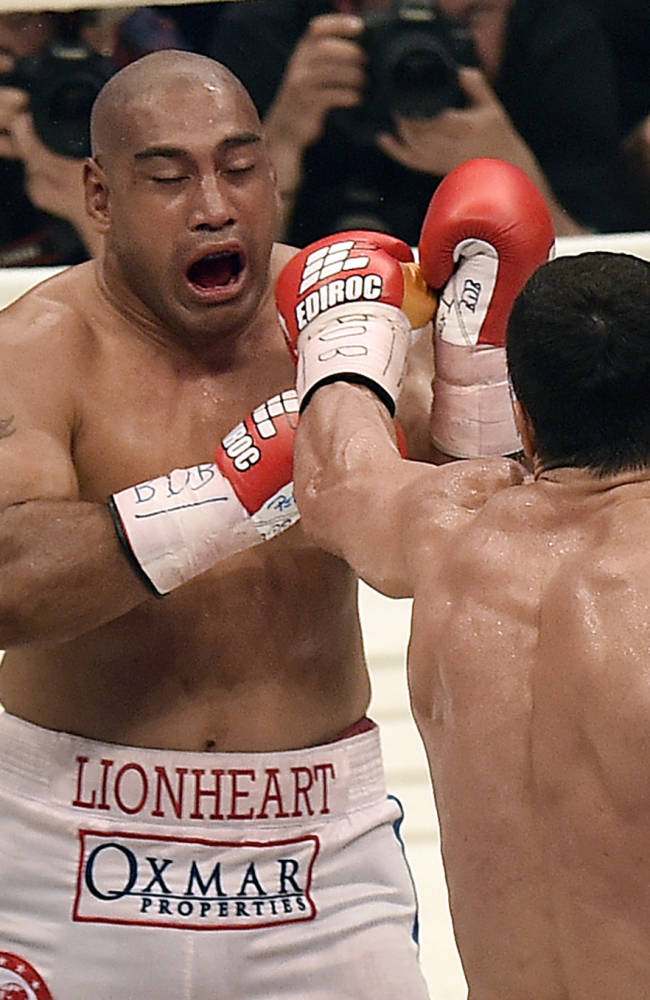 World boxing champion Wladimir Klitschko of Ukraine, right, punches Samoan-born Australian challenger Alex Leapai during their IBF, IBO, WBO and WBA heavyweight title bout in Oberhausen, Germany, Saturday, April 26, 2014. Klitschko won the fight by technical knock out in the fifth round