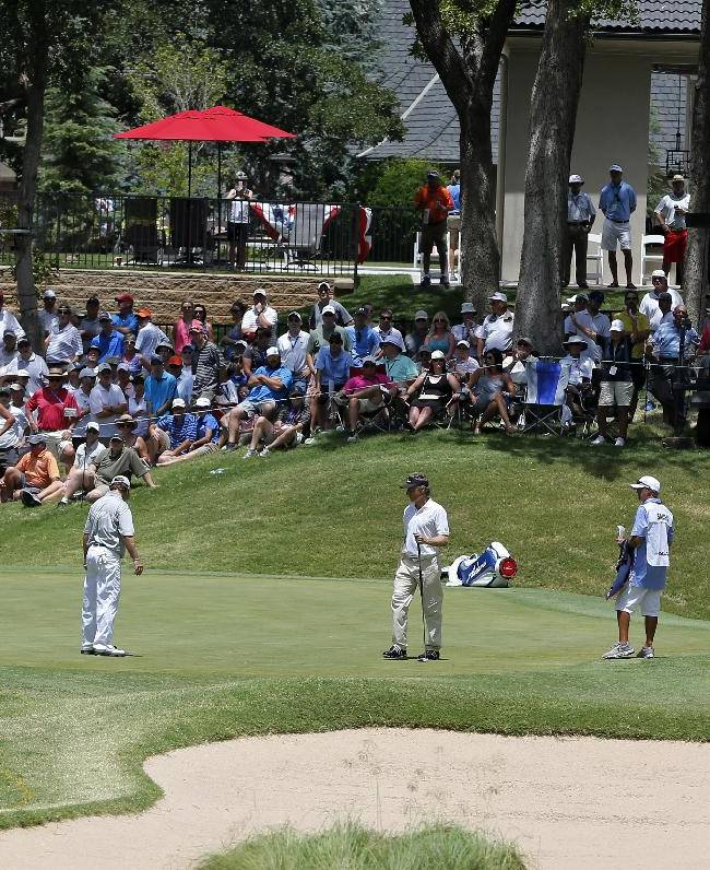 Gene Sauers, second from left, and Bernhard Langer, second from right, look over the fourth green during the third round of play at the 2014 U.S. Senior Open golf tournament at Oak Tree National in Edmond, Okla., Saturday, July 12, 2014