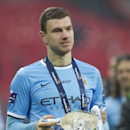Manchester City's Edin Dzeko holds the winners trophy as he celebrates after his team's 3-1 win against Sunderland in the League Cup Final at Wembley Stadium, London, England, Sunday March 2, 2014