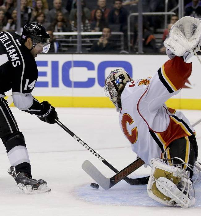Calgary Flames goalie Karri Ramo, right, blocks a shot by Los Angeles Kings right wing Justin Williams during the second period of an NHL hockey game in  Los Angeles, Monday, Oct. 21, 2013