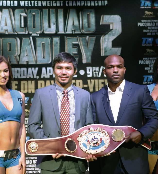 Boxer Manny Pacquiao, second from left, of the Phillipines, left, poses two Top TRank Knockout girls and his opponent Timothy Bradley of Indio, Ca., current WBO World Welterweight champion during a press conference, Thursday, Feb. 6, 2014, in New York.  The pair will face off for a second time in a title fight April 12, 2014, in Las Vegas. Bradley won their first encounter