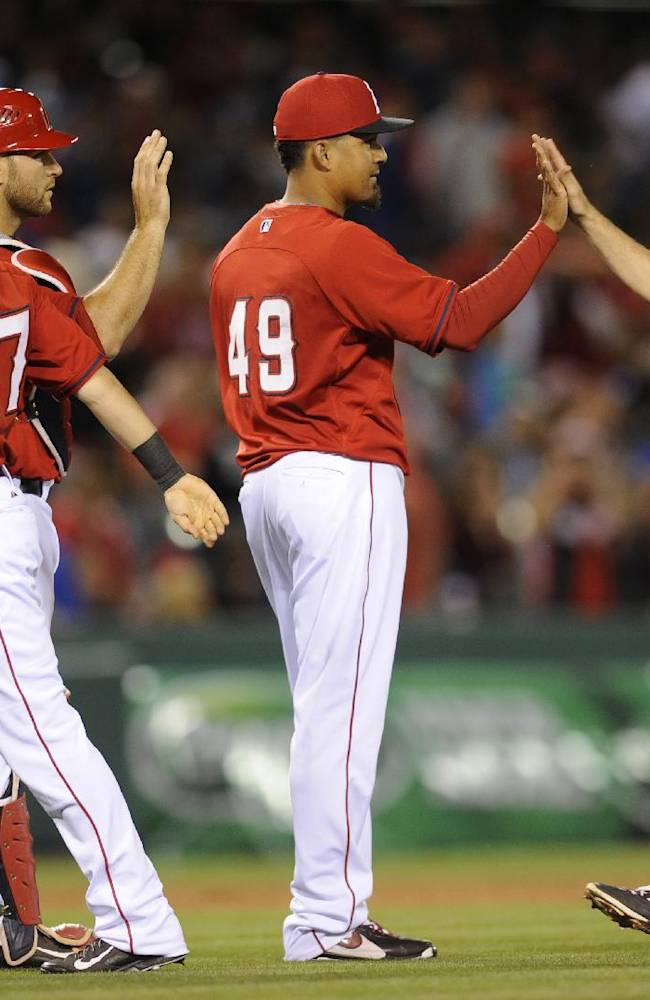 Los Angeles Angels relief pitcher Ernesto Frieri, center, celebrates with shortstop John McDonald, right, after the Angels defeated the Los Angeles Dodgers 6-2 in anexhibition baseball game in Anaheim, Calif., Saturday, March 29, 2014