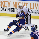 Chicago Blackhawks right wing Marian Hossa (81) hooks New York Islanders left wing Matt Martin (17) in the third period of an NHL hockey game at Nassau Coliseum on Saturday, Dec. 13, 2014, in Uniondale, N.Y. The Islanders won 3-2 The Associated Press
