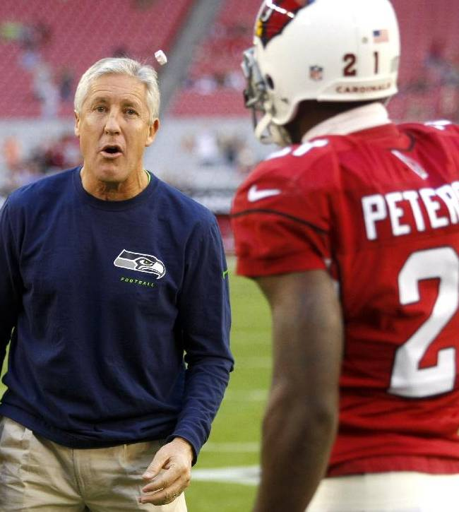 Seattle Seahawks coach Pete Carroll tosses a piece of gum to Arizona Cardinals cornerback Patrick Peterson (21) before an NFL football game Thursday, Oct. 17, 2013, in Glendale, Ariz