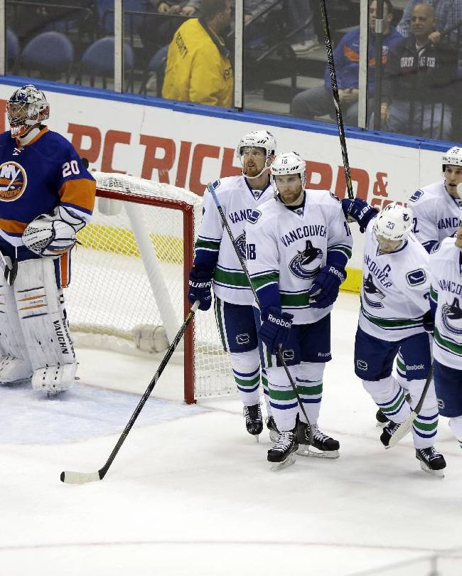 New York Islanders goalie Evgeni Nabokov (20) reacts after Vancouver Canucks' Daniel Sedin, second from left, scored during the second period of an NHL hockey game as teammates Ryan Stanton (18), Henrik Sedin (33), Kevin Bieksa (3) and Dale Weise (32) skate away Tuesday, Oct. 22, 2013 in Uniondale, N.Y