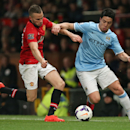 Manchester City's Samir Nasri, right, battles for the ball with Manchester United's Tom Cleverley during the English Premier League soccer match at Old Trafford, Manchester EnglandTuesday March 25, 2014