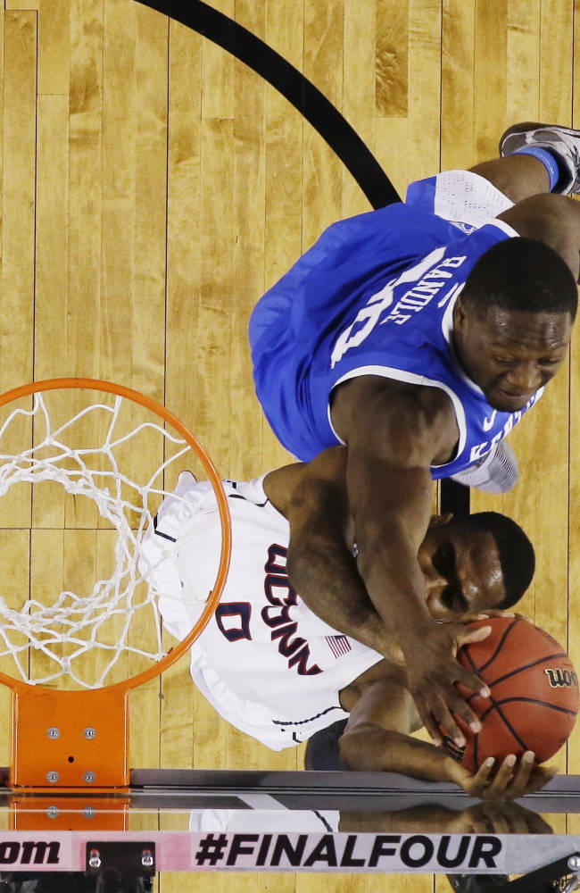 Kentucky forward Julius Randle (30) tries to block the ball from Connecticut forward Phillip Nolan (0) during the first half of the NCAA Final Four tournament college basketball championship game Monday, April 7, 2014, in Arlington, Texas