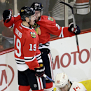 Chicago Blackhawks left wing Brandon Saad (20) celebrates with center Jonathan Toews (19) after scoring a goal as Calgary Flames center Josh Jooris (86) reacts during the third period of an NHL hockey game in Chicago, Sunday, Dec. 14, 2014. The Blackhawks