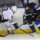 St. Louis Blues' T.J. Oshie (74) and Chicago Blackhawks' Patrick Sharp (10) reach for the puck during the second period in Game 2 of a first-round NHL hockey playoff series on Saturday, April 19, 2014, in St. Louis. (AP Photo/Bill Boyce)