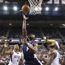 Memphis Grizzlies guard Tony Allen, center, drives to the basket between Sacramento Kings' Chuck Hayes, left, and DeMarcus Cousins during the first quarter of an NBA basketball game in Sacramento, Calif., Sunday, Nov. 17, 2013 The Associated Press