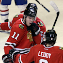 Chicago Blackhawks' Jeremy Morin (11) celebrates with Nick Leddy (8) and Brandon Bollig (52) after scoring his goal during the third period of an NHL hockey game against the Montreal Canadiens in Chicago, Wednesday, April 9, 2014. The Blackhawks won 3-2 i