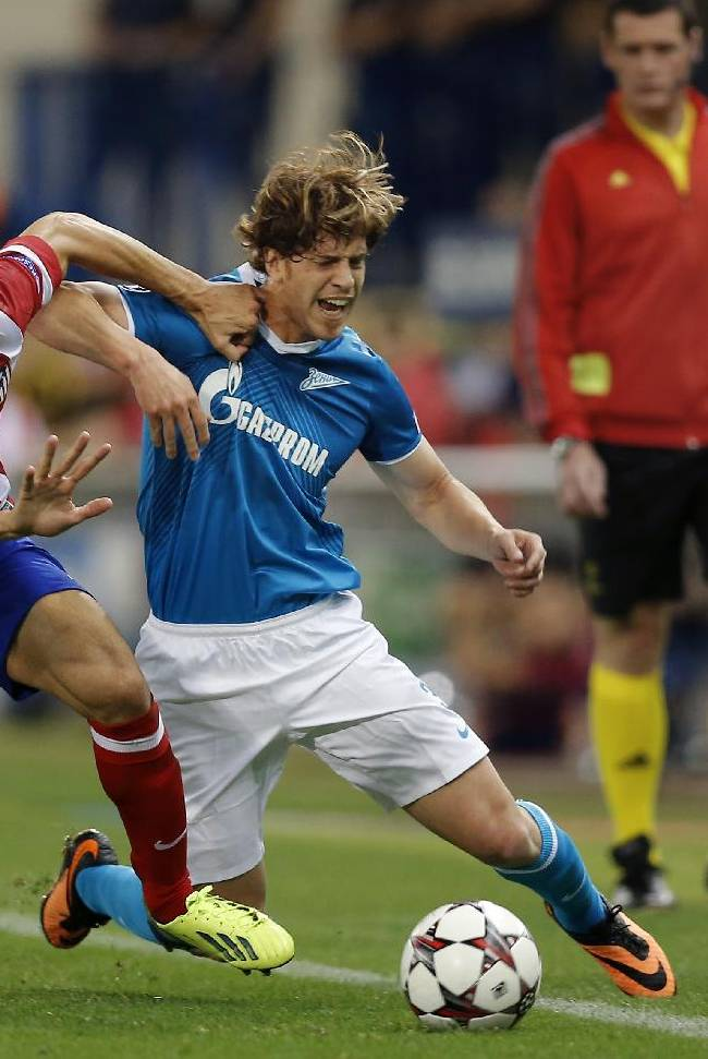 Atletico Madrid's Juanfran, left, duels for the ball with Zenit St. Petersburg Cristian Ansaldi during a Group G Champions League soccer match  at the Vicente Calderon stadium in in Madrid, Spain, Wednesday, Sept. 18, 2013