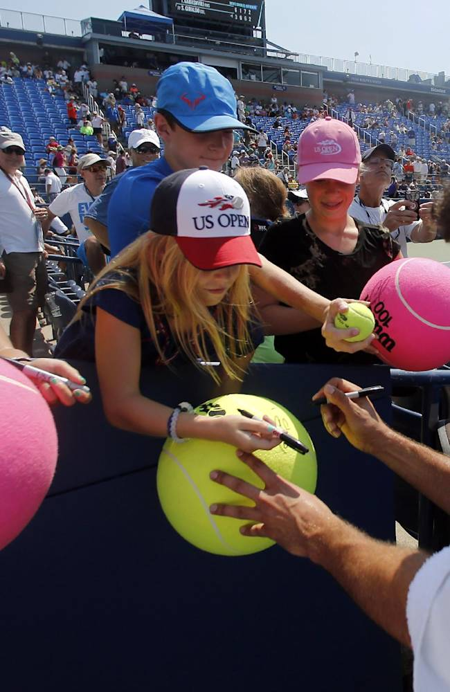 Marin Cilic, of Croatia, signs autographs for fans after winning by forfeit in the second set over Marcos Baghdatis, of Cyprus, during the second round of the 2014 U.S. Open tennis tournament, Wednesday, Aug. 27, 2014, in New York