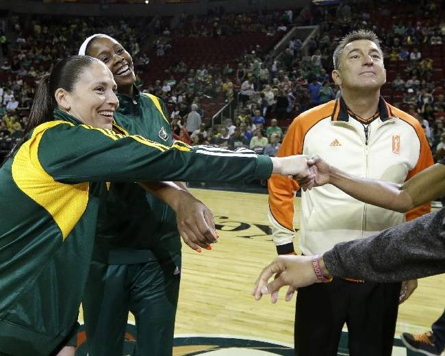 Seattle Storm's Sue Bird, left, and Camille Little shake hands with Los Angeles Sparks players as an official stands nearby before a WNBA basketball game Friday, May 16, 2014, in Seattle. The game was Bird's first since the 2012 season