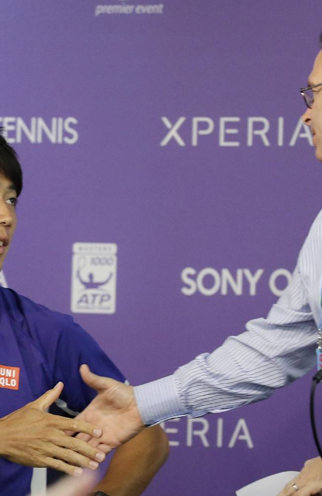 Kei Nishikori, of Japan, left, shakes hands with tournament director Adam Barrett, right, following a news conference after he withdrew from his semifinal match against Novak Djokovic due to a left groin injury at the Sony Open tennis tournament, Friday, March 28, 2014, in Key Biscayne, Fla