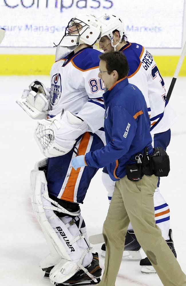 A trainer helps Edmonton Oilers goalie Ilya Bryzgalov (80) off the ice after he was hit hard during the first period of an NHL hockey game against the Dallas Stars, Sunday, Dec. 1, 2013, in Dallas. The Oilers won 3-2