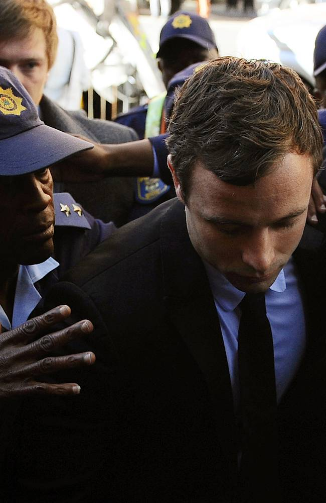 FILE: In this Monday, Aug. 19, 2013 Oscar Pistorius, centre, arrives outside the magistrates court in Pretoria, South Africa where he was indicted on charges of murder and illegal possession of ammunition for the shooting death of his girlfriend Reeva Steenkamp. With his athletic triumphs tarnished by the killing Pistorius, now 27, faces possibly being sent to prison until he is older than 50. Pistorius goes on trial Monday March 3, 2014. (AP Photo-File)
