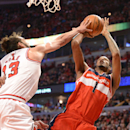 Chicago Bulls center Joakim Noah (13) gets a hand on a shot by Washington Wizards forward Trevor Ariza (1) during Game 2 in an opening-round NBA basketball playoff series Tuesday, April 22, 2014, in Chicago. The Wizards won 101-99 The Associated Press