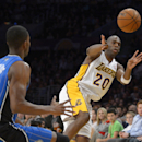 Los Angeles Lakers guard Jodie Meeks, left, passes the ball as Orlando Magic forward Maurice Harkless defends during the first half of an NBA basketball game, Sunday, March 23, 2014, in Los Angeles The Associated Press