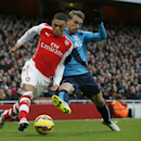 Arsenal's Alex Oxlade-Chamberlain, left, controls the ball past Stoke City's Marc Muniesa during their English Premier League soccer match between Arsenal and Stoke City at the Emirates stadium in London, Sunday, Jan. 11, 2015