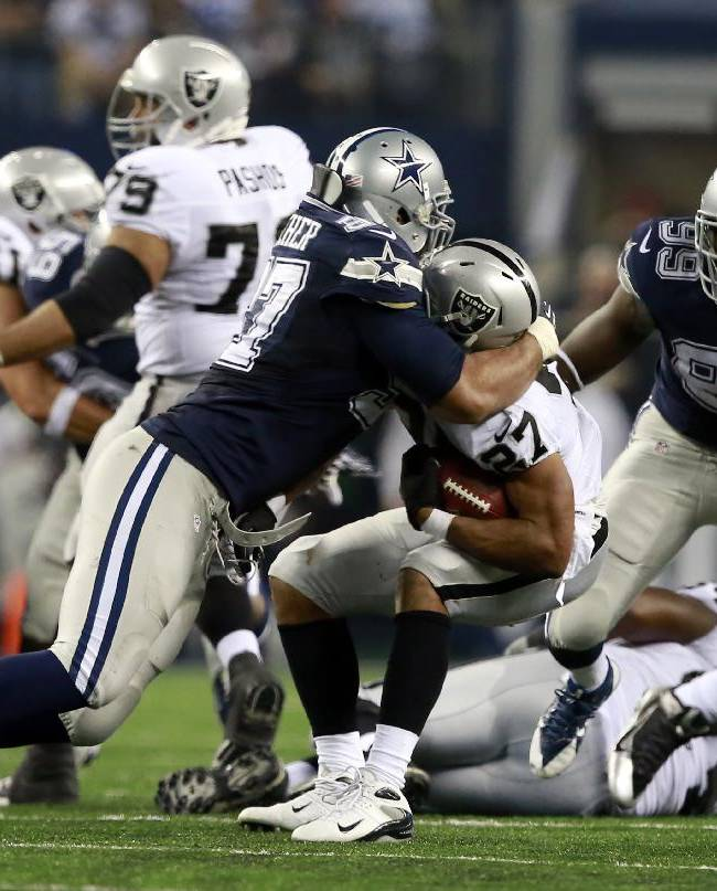 Oakland Raiders running back Rashad Jennings (27) is tackled by Dallas Cowboys defensive tackle Jason Hatcher during the second half of an NFL football game Thursday, Nov. 28, 2013, in Arlington, Texas