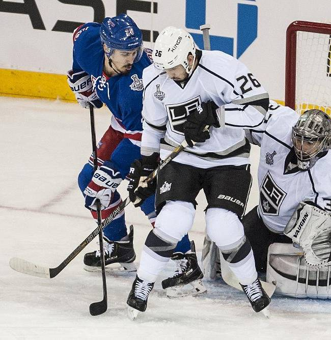 Chris Kreider of the Rangers and Slava Voynov battle for the puck in front of Jonathan Quick during first period action as the Los Angeles Kings play the New York Rangers in Game 4 of the Stanley Cup Finals Wednesday night June 11, 2014 at Madison Square Garden in New York