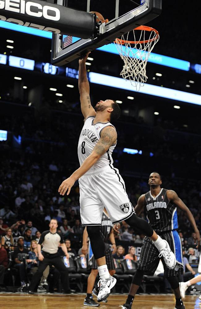 Brooklyn Nets' Deron Williams (8) shoots in front of Orlando Magic's Dewayne Dedmon (3) during the first half of an NBA basketball game Sunday, April 13, 2014, in New York