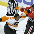 Philadelphia Flyers right wing Wayne Simmonds, left, and Chicago Blackhawks defenseman Sheldon Brookbank, right, fight during the first period of an NHL hockey game on Wednesday, Dec. 11, 2013, in Chicago. (AP Photo/Charles Rex Arbogast)