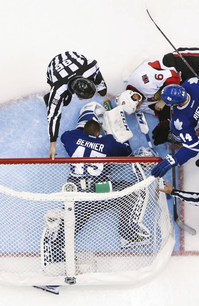 Ottawa Senators' Bobby Ryan (6) falls over with the net on top of Toronto Maple Leafs goalie Jonathan Bernier (45) as Maple Leafs' Morgan Rielly, right, and Nazem Kadri, left, look on during third-period action of an NHL hockey game in Toronto, Saturday, Oct. 5, 2013. (AP photo/The Canadian Press, Mark Blinch)