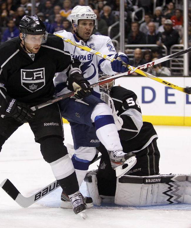 Los Angeles Kings defenseman Jake Muzzin (6) sandwiches in Tampa Bay Lightning right wing Martin St. Louis (26) with Kings goalie Ben Scrivens (54) defending in the third period of an NHL hockey game Tuesday, Nov. 19, 2013, in Los Angeles. The Kings won 5-2