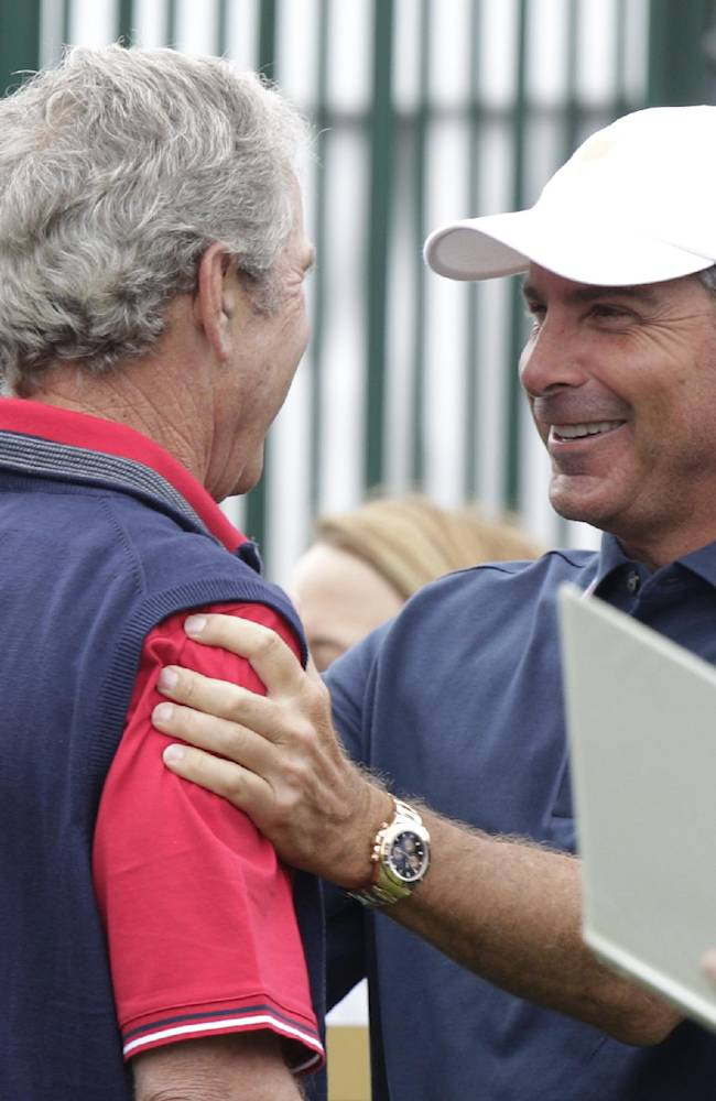 Former President George W. Bush, left, talks with United States team captain Fred Couples before the start of the four-ball match at the Presidents Cup golf tournament at Muirfield Village Golf Club Thursday, Oct. 3, 2013, in Dublin, Ohio