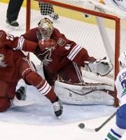 Phoenix Coyotes' Mike Smith (41) and Oliver Ekman-Larsson (23), of Sweden, move into position to protect the goal as Vancouver Canucks' Daniel Sedin (22), also of Sweden, tries to control the puck to get a shot off during the second period of an NHL hockey game on Thursday, Jan. 16, 2014, in Glendale, Ariz. (AP Photo/Ross D. Franklin)