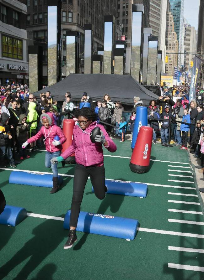 Football fans run an obstacle course on Super Bowl Boulevard, 13 blocks of entertainment activity stretching from 47th Street to 34th Street, Saturday Feb. 1, 2014, in New York