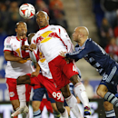 New York Red Bulls defender Jamison Olave (4) heads the ball away from Sporting Kansas City defender Aurelien Collin (78) in the second half during an MLS playoff soccer match at Red Bull Arena in Harrison, N.J., Thursday, Oct. 30, 2014. The Red Bulls def