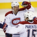Montreal Canadiens' Pierre-Alexandre Parenteau, right, celebrates with teammate Travis Moen after scoring the winning goal against the Calgary Flames during a shootout in an NHL hockey game, Tuesday, Oct. 28, 2014 in Calgary, Alberta The Associated Press